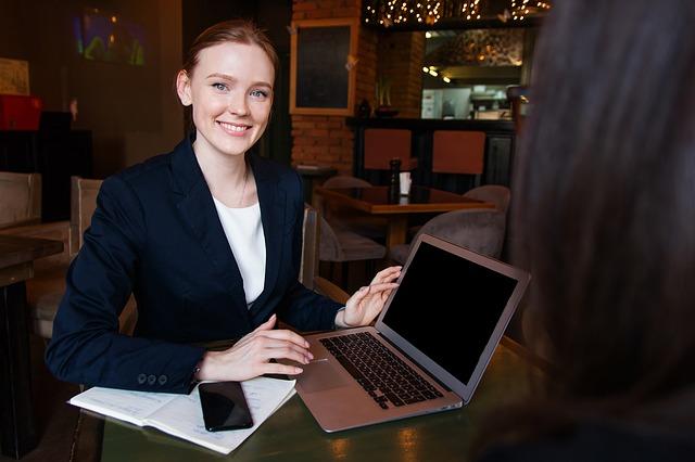 Žena v bielom tričku a elegantnom čiernom kostýme sedí pri stole s notebookom.jpg